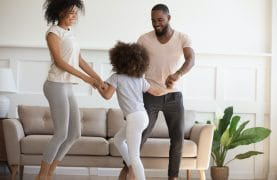 Funny active family with little kid dancing in living room