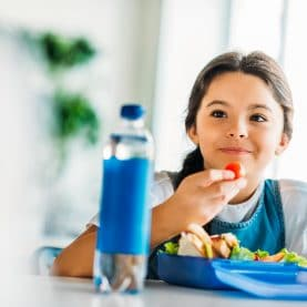 young girl eating lunch at school