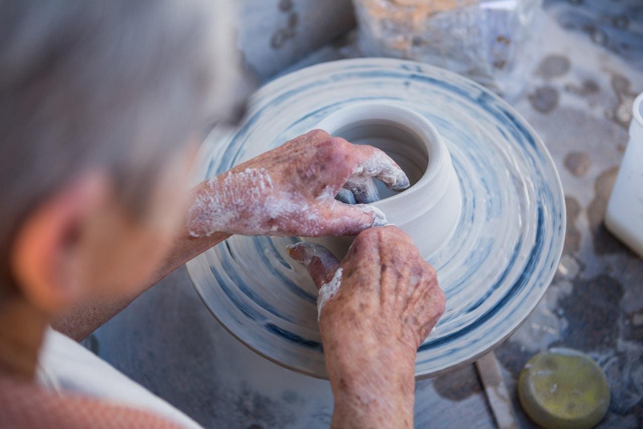 older adult making pottery